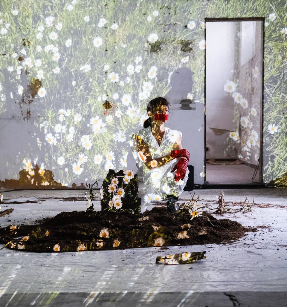 yael in an abandoned house, painted flowers cover the walls, she crouches in a soil bed
