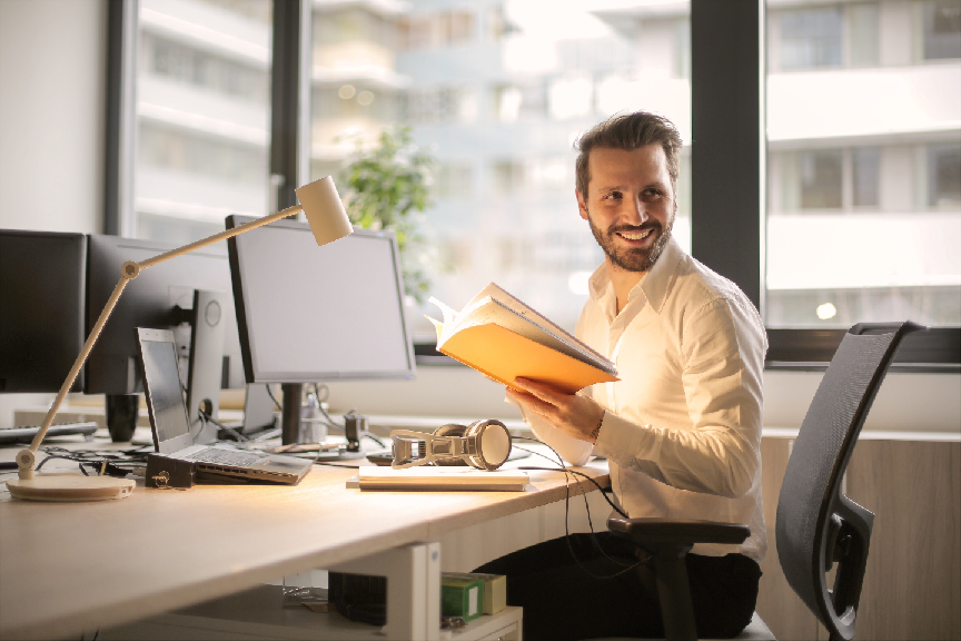 young business man at his desk reading a book in front of his computer, looking around and smiling at something behind him