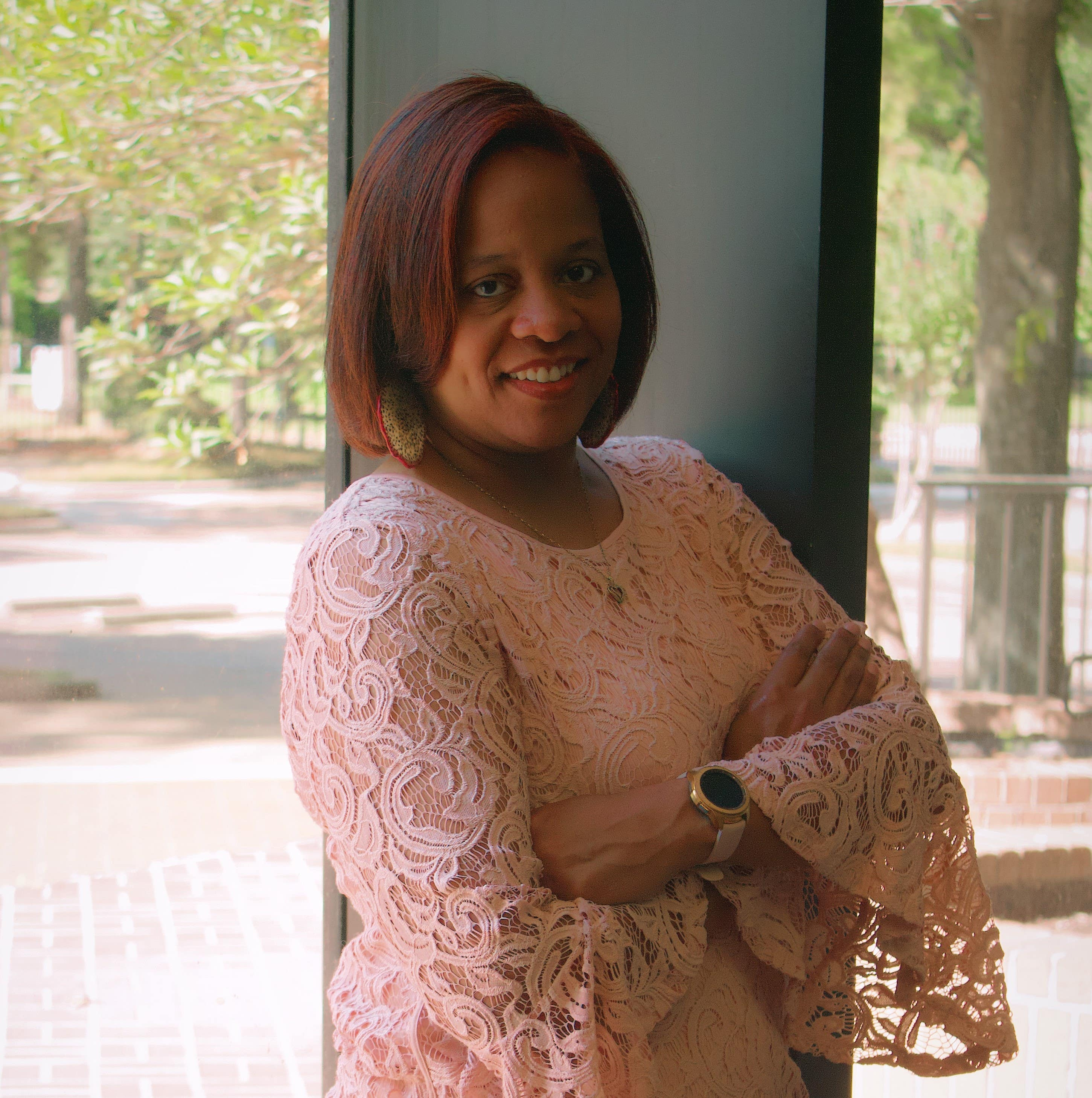 Course founder TaJuana Antwine stands by a window in a pink lace blouse