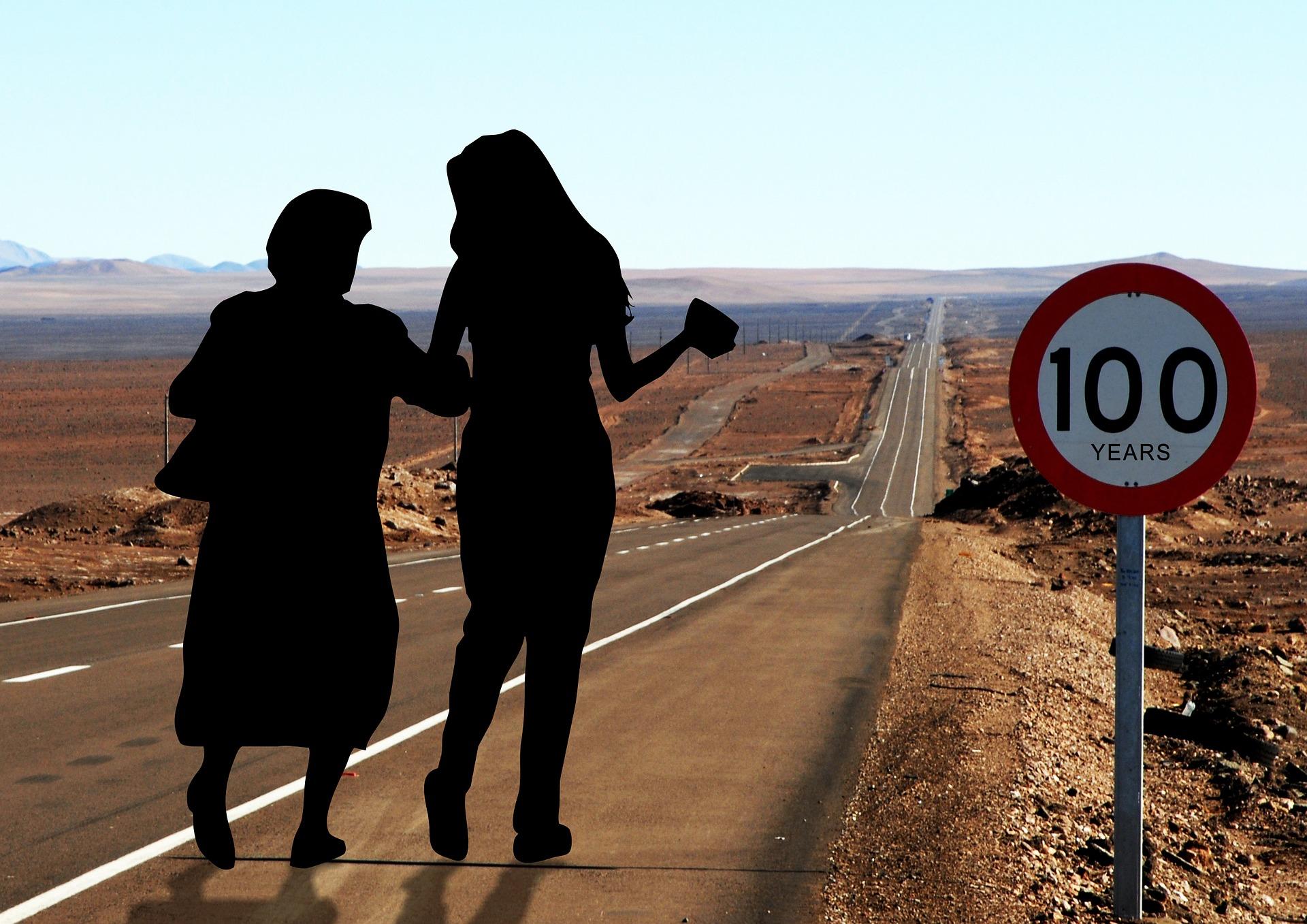Vanhan ja nuoren naisen silhuetti maantiellä