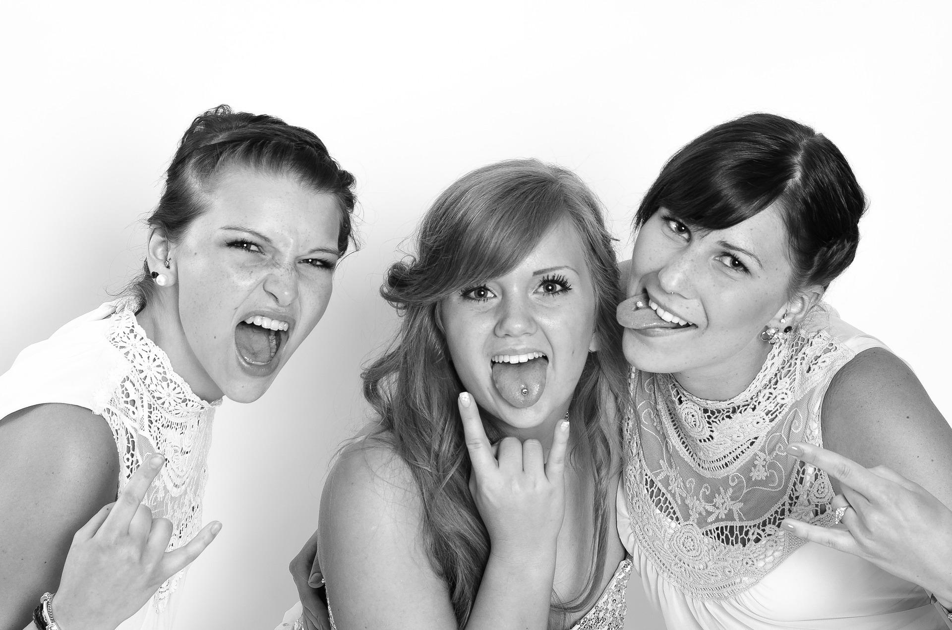 3 naista, ystävystä villin iloisina, näyttävät kieltä ja heavy-tervehdystä