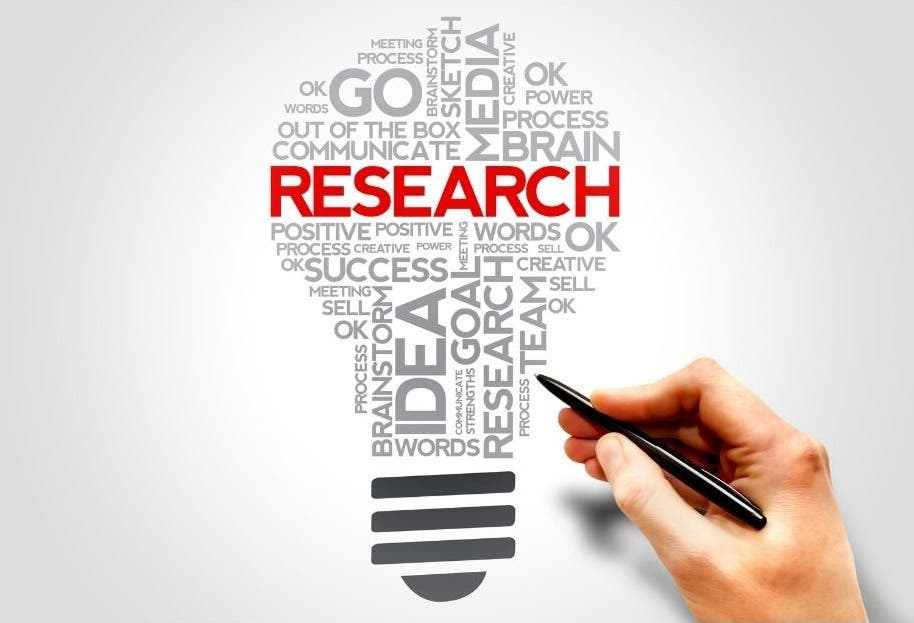 A hand writing the word research in the shape of a lightbulb