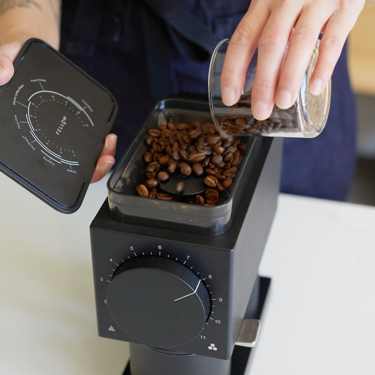 hand pouring grinds into Fellow Ode Grinder