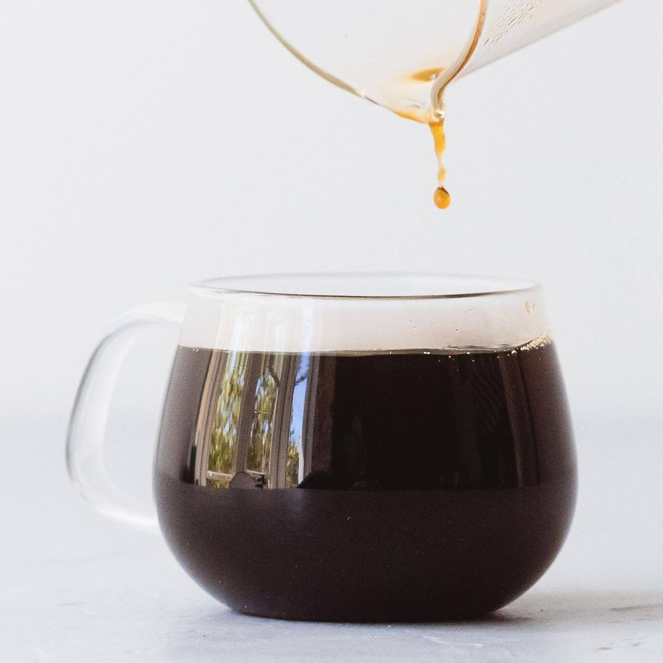 black coffee in glass mug, last drop falling from glass carafe above mug