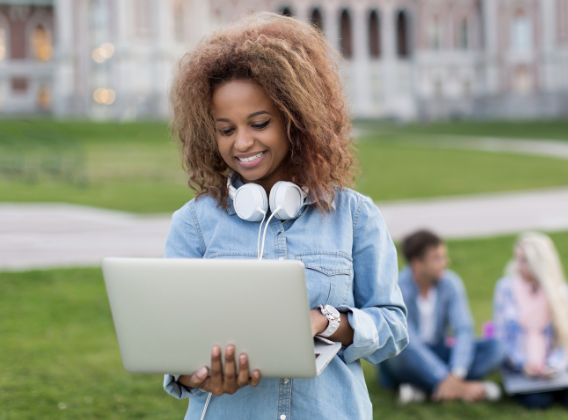 A smiling student standing outside types on her laptop.