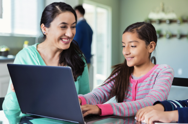 A smiling mother and daughter pair work at a laptop together.