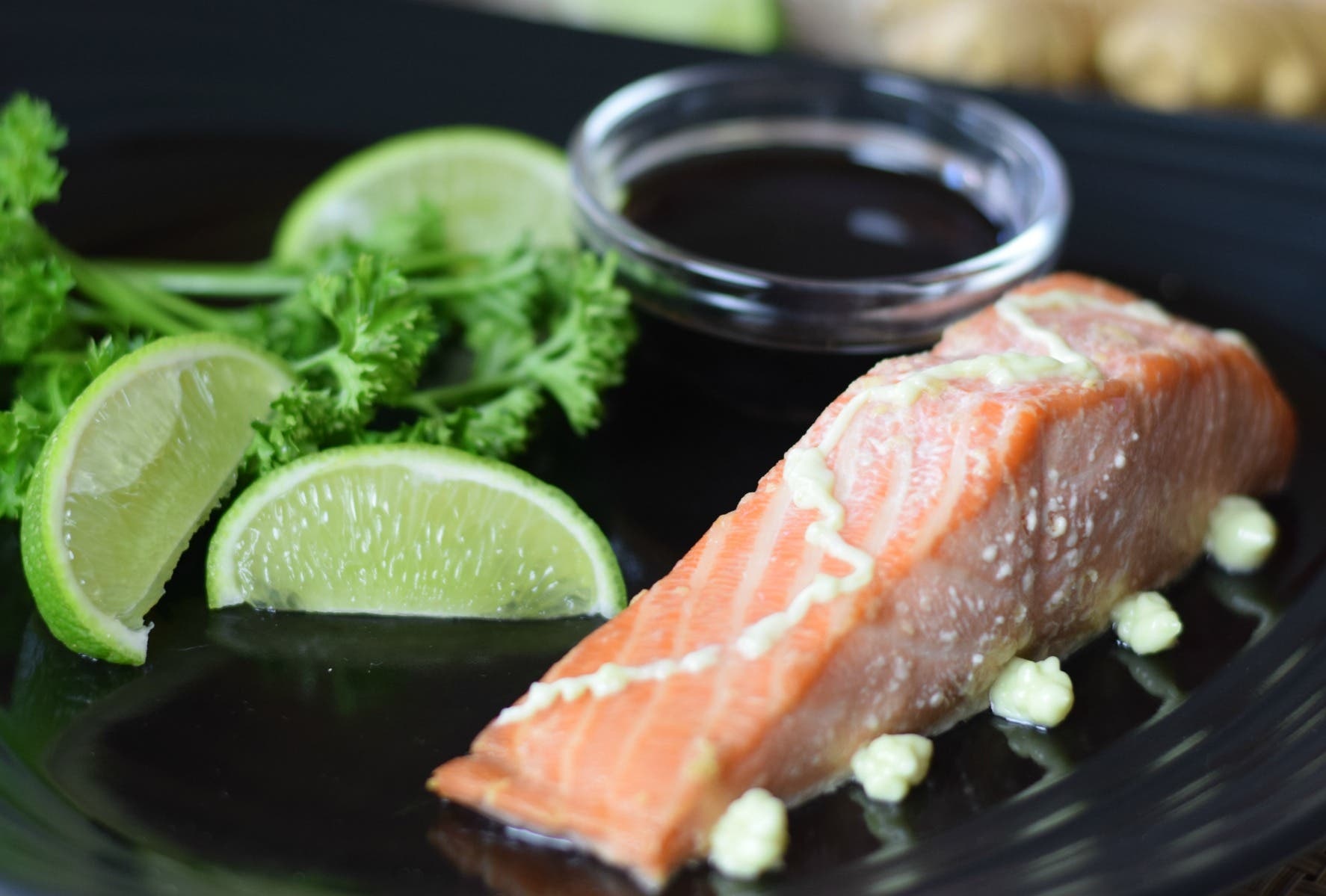 salmon with wasabi on a black plate with lime and parsley