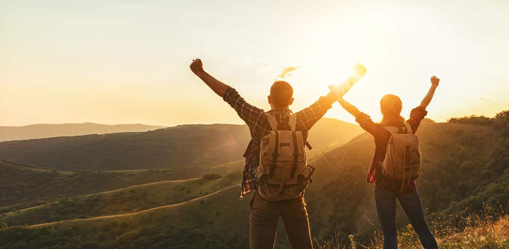 two hikers with hands up at sunset viewing small mountain range