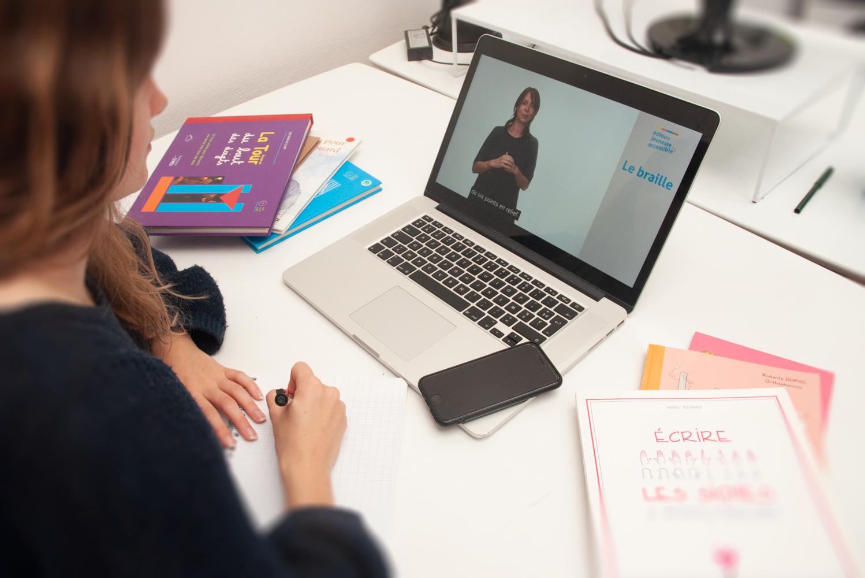 Photo d'une apprenante sur son ordinateur à son bureau