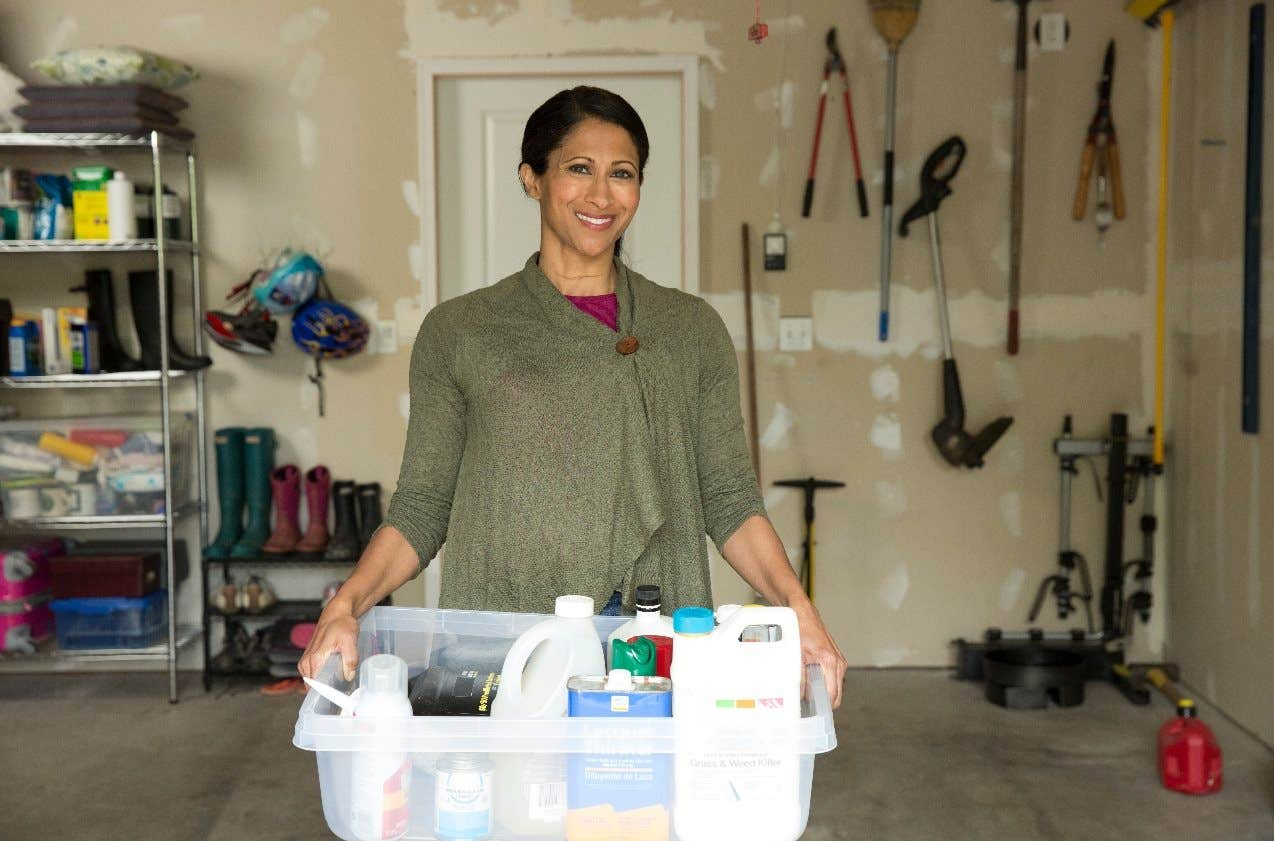 woman in garage holding tub of chemicals