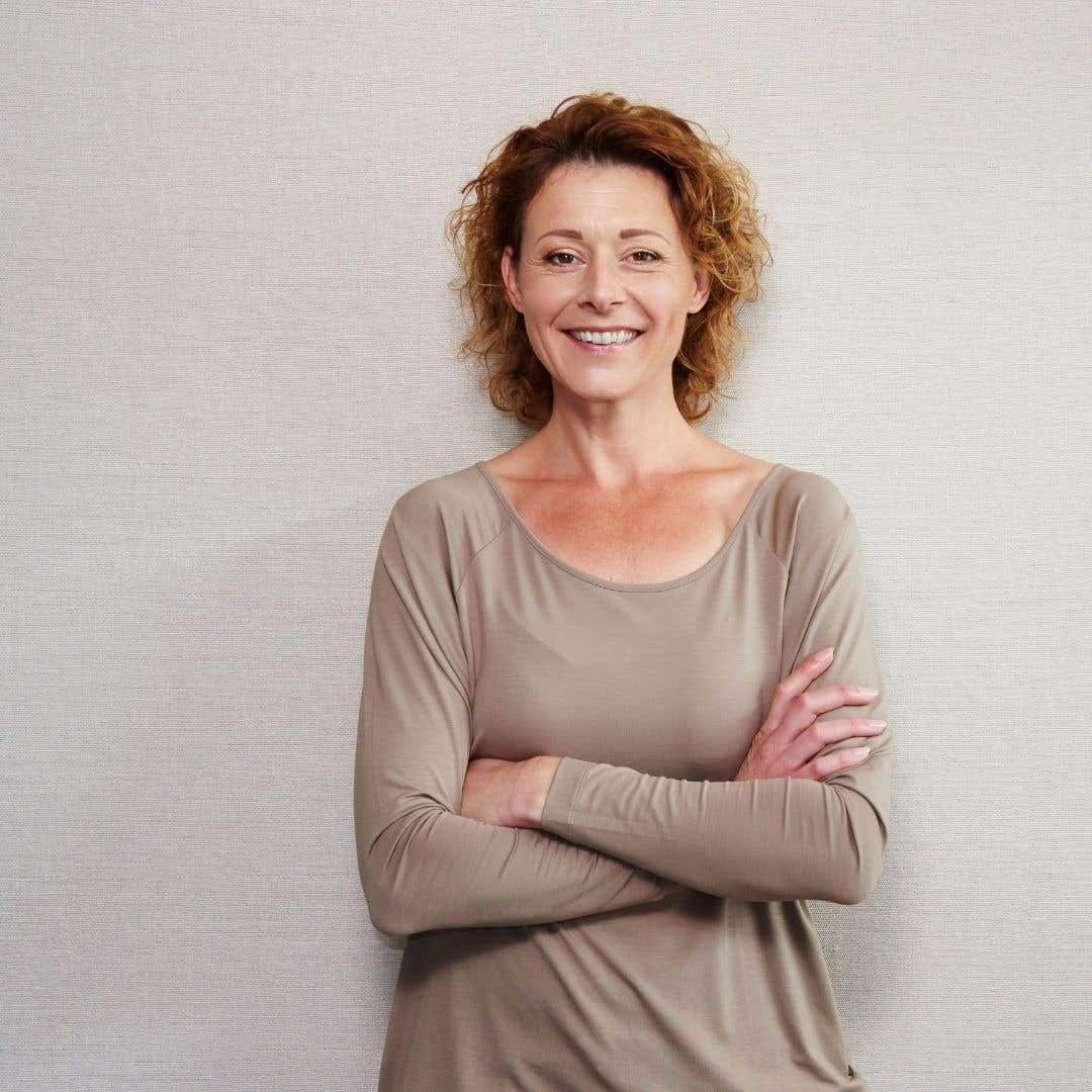 Confident therapist, smiling with folded arms against a neutral background