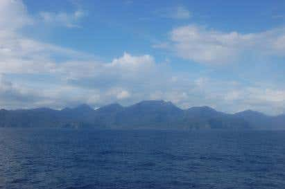 ocean water leading to a distant outline of grass covered mountains.