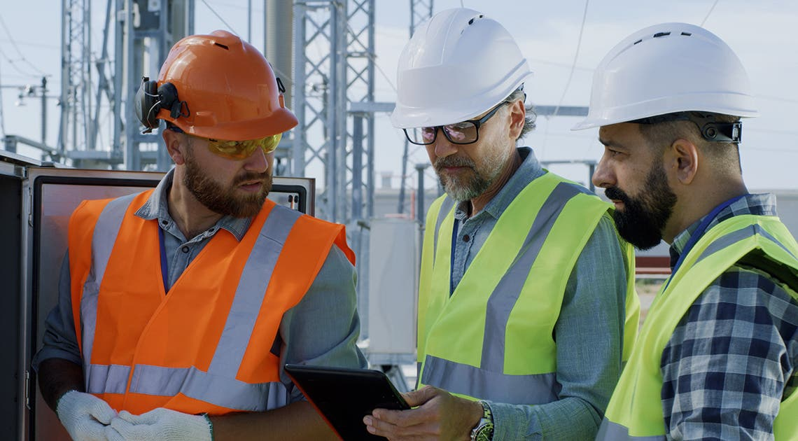Three people having a discussion on a construction site