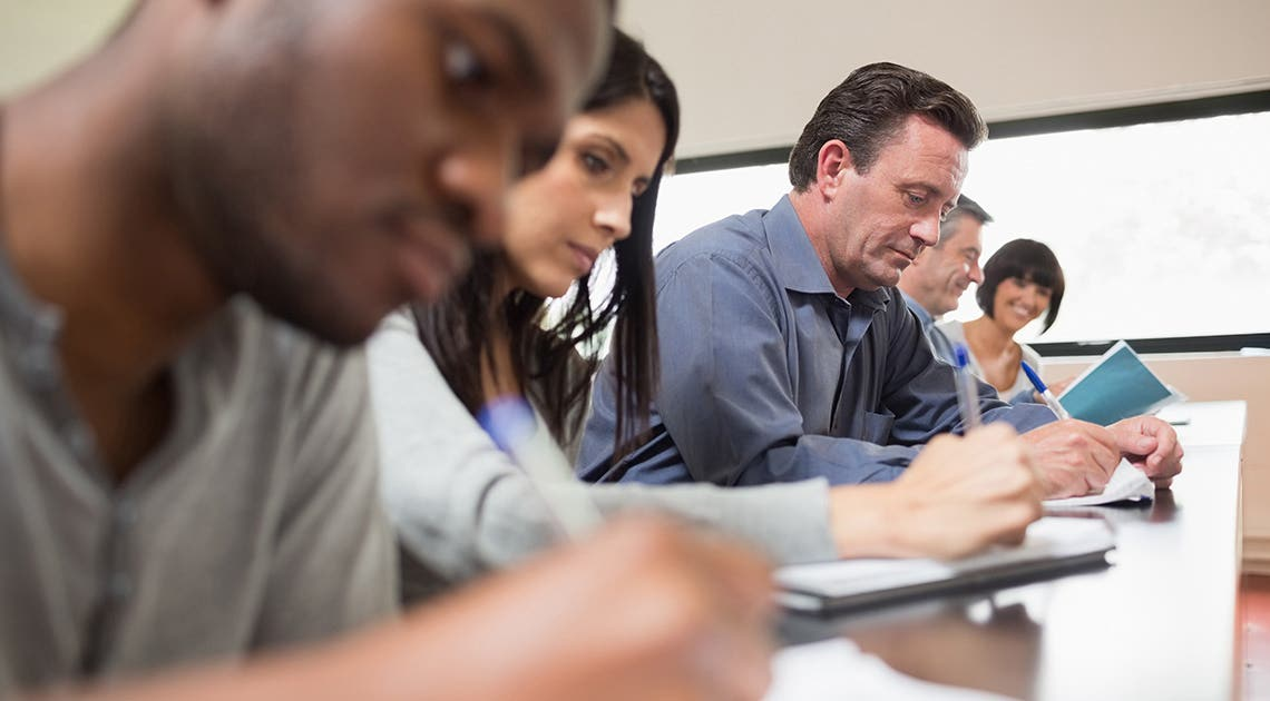 Multiple people taking notes in a classroom