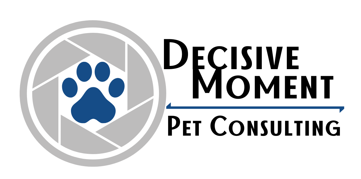 company logo of a grey camera aperture, with a blue paw print in the middle. The words Decisive Moment Pet Consulting is to the left.