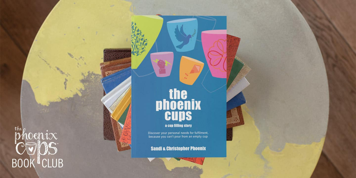 The Phoenix Cups book is placed on the top of a pile of books, atop a funky circular coffee table that has an Atlas painted on it.