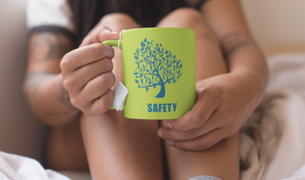 A woman sitting in a quilt holding a green mug labelled SAFETY with a tea bag in it.