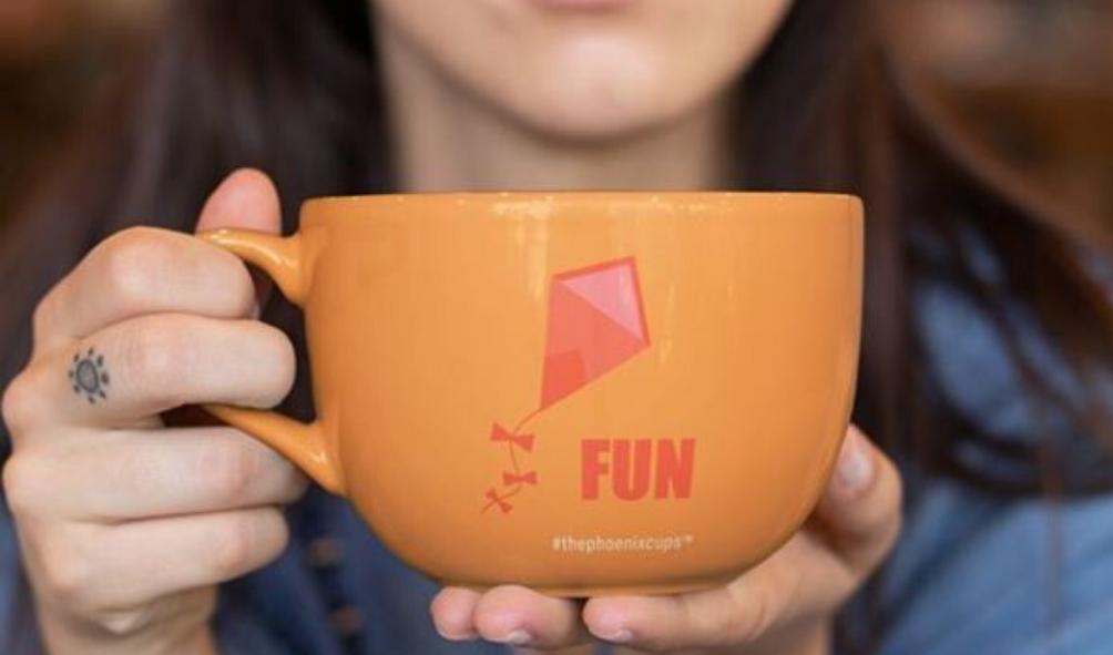 A woman holding a big mug that says FUN