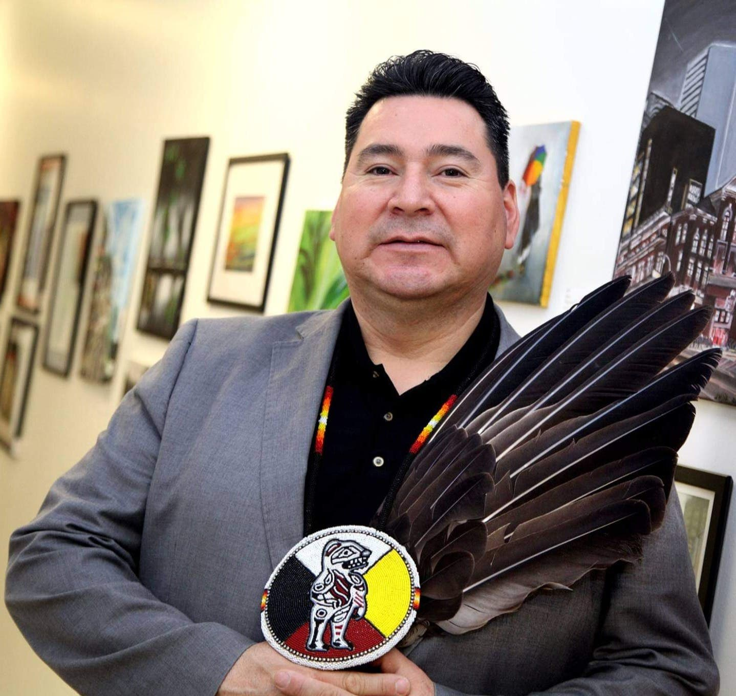 Bear Standing Tall holding bald eagle feather